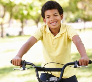 Young boy on a bike smiling wearing his traditional braces to fix his smile.